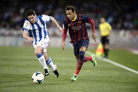 Barcelona's Neymar (R) fights for the ball with Real Sociedad's Zaldua during their Spanish first division soccer match at Anoeta stadium in San Sebastian February 22, 2014. REUTERS/Vincent West
