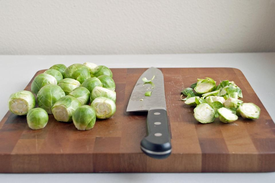 <p>Slice off the tough woody stems. This is particularly important if you're eating the shredded brussels sprouts raw, but it will also help make it easier to separate the shredded layers later.</p>
