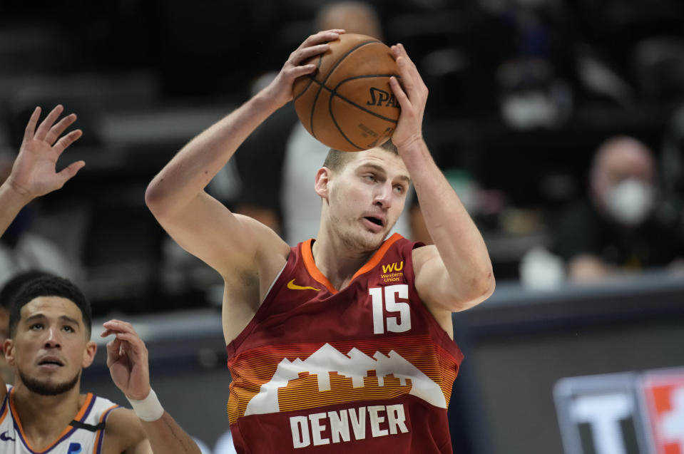 Denver Nuggets center Nikola Jokic, right, pulls in a rebound in front of Phoenix Suns guard Devin Booker in the first half of Game 4 of an NBA second-round playoff series Sunday, June 13, 2021, in Denver. (AP Photo/David Zalubowski)