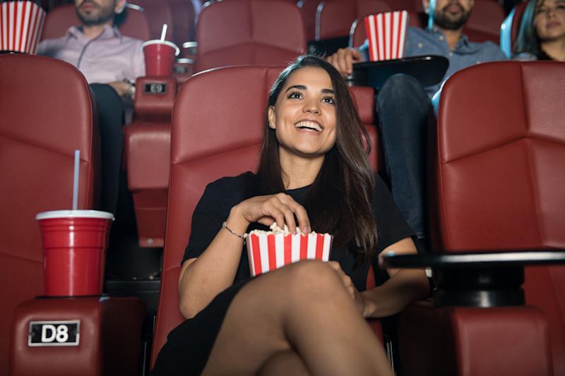 Gorgeous young Hispanic woman having fun watching a comedy film and laughing at the movie theater