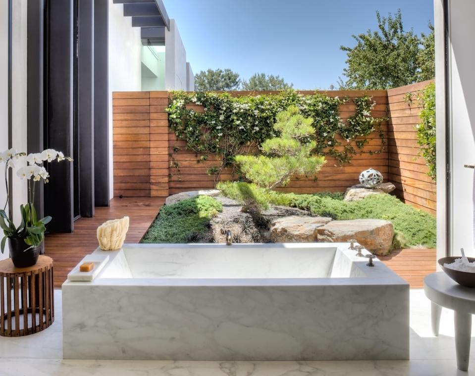"""""""'I'm all about cozy and comfort,' Jen said. Sexy and fun were also part of her design lexicon,"""" Shadley writes. In Aniston's master bedroom, a deep stone tub looked out over a walled-in Zen garden. A simple press of a button retracted the floor-to-ceiling window for an open-air experience."""