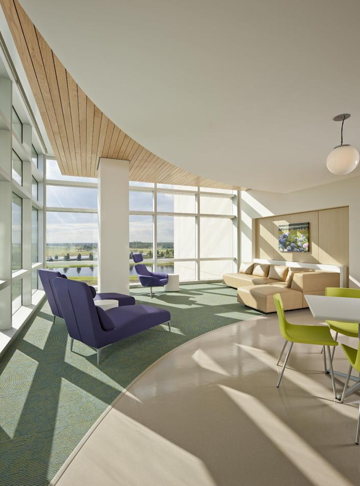 This undated photo provided by Perkins+Will shows the waiting area at Orlando's Nemours children's hospital, with rich hues, contemporary yet comfortable seating and natural light via floor to ceiling windows. (Jonathan Hillyer Photography/Perkins+Will via AP)