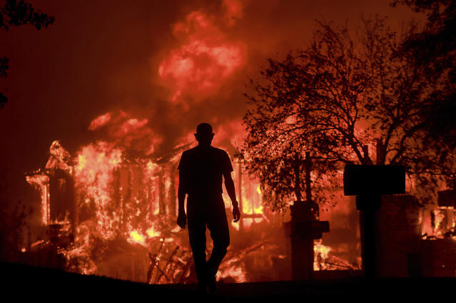 <p>Jim Stites watches part of his neighborhood burn in Fountaingrove, Calif., Monday Oct. 9, 2017. More than a dozen wildfires whipped by powerful winds been burning though California wine country. The flames have destroyed at least 2,000 homes and businesses and sent thousands of people fleeing. (Photo: Kent Porter/The Press Democrat via AP) </p>