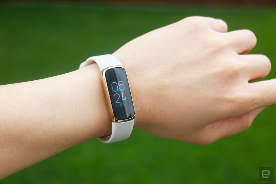 <p>The Fitbit Luxe with a light pink silicone band on a wrist against a grassy green background. The screen shows the time is 6:24pm.</p>