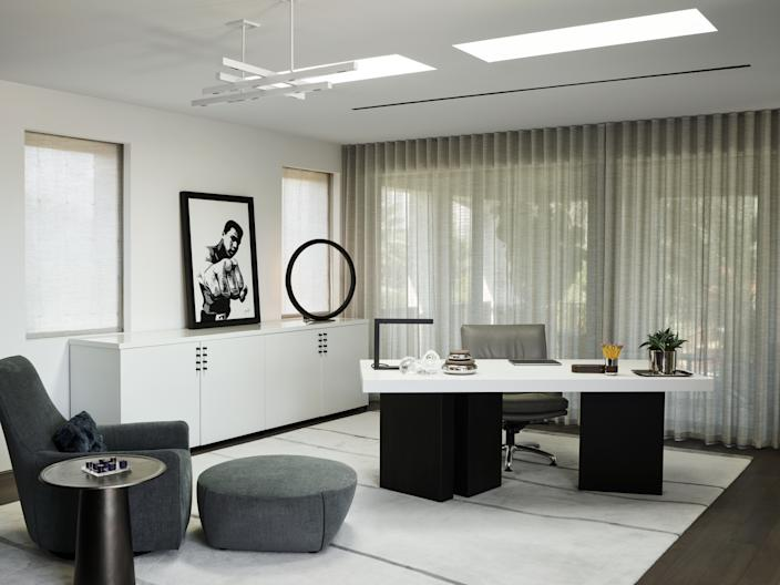 """<div class=""""caption""""> Now that Joyner is semi-retired, he works out of his home office. He insisted on adding the skylights in the ceiling to make the room even brighter. The desk and cabinet were custom designed by Wecselman Design and paired with a rug from <a href=""""https://artandloom.com/"""" rel=""""nofollow noopener"""" target=""""_blank"""" data-ylk=""""slk:Art and Loom"""" class=""""link rapid-noclick-resp"""">Art and Loom</a>, a side table from <a href=""""https://www.hollyhunt.com/"""" rel=""""nofollow noopener"""" target=""""_blank"""" data-ylk=""""slk:Holly Hunt"""" class=""""link rapid-noclick-resp"""">Holly Hunt</a>, and a club chair and ottoman from <a href=""""https://www.minotti.com/en"""" rel=""""nofollow noopener"""" target=""""_blank"""" data-ylk=""""slk:Minotti"""" class=""""link rapid-noclick-resp"""">Minotti</a>. The painting is <em>Ali,</em> by Stephen Bates. </div>"""