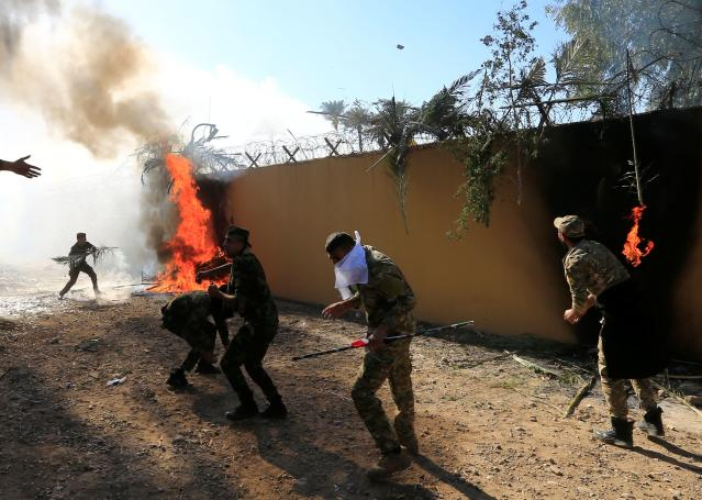 Hashd al-Shaabi (paramilitary forces) fighters set the U.S. Embassy wall on fire as they protest to condemn air strikes on their bases, in Baghdad, Iraq December 31, 2019. (Photo: Thaier al-Sudani/Reuters)