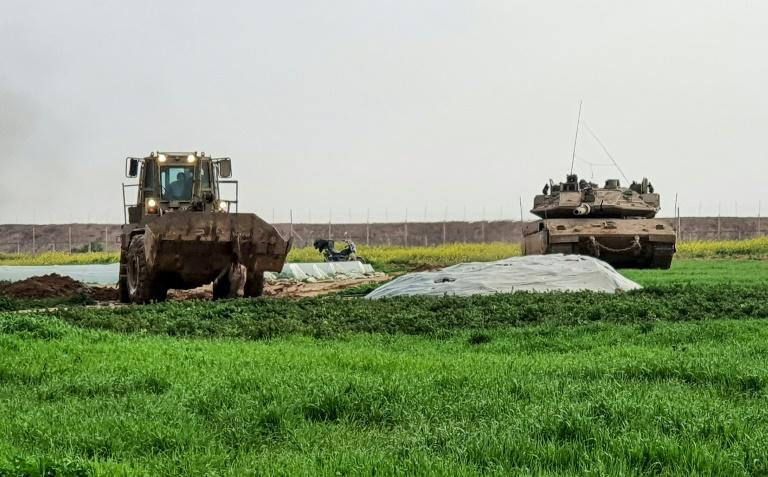 This picture taken with a mobile phone shows an Israeli bulldozer carrying the body of a Palestinian shot dead by Israeli forces after he was suspected of placing a bomb along the Gaza-Israel border (AFP Photo/MUTHANA AL-NAJAAR)
