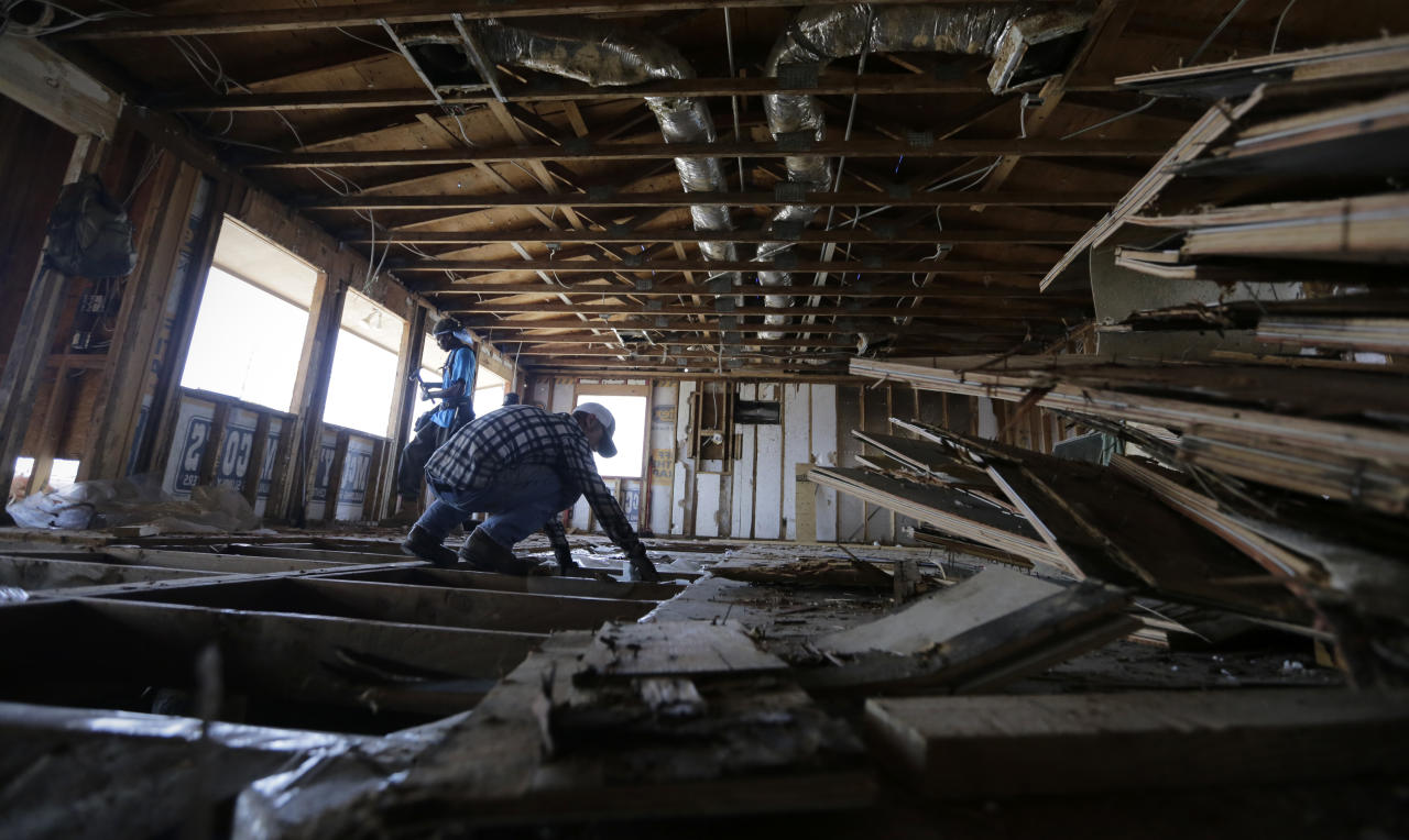 In this Friday, Sept. 29, 2017 photo, a crew works clear debris from the Island Cafe that was damaged by Hurricane Harvey, in Port Aransas, Texas. Tourists are expected to stay away through the holidays, and even the possibility of getting back to business by Spring Break looks bleak. (AP Photo/Eric Gay)