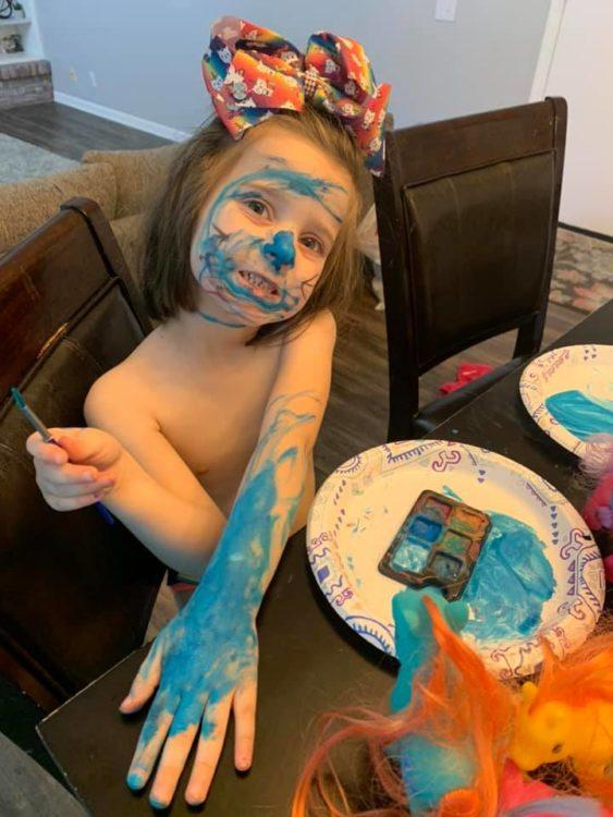 Little girl with paint all over face and body