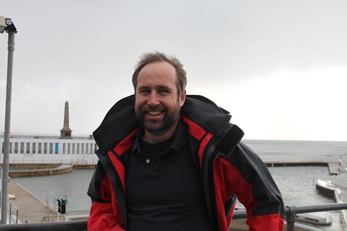 Jon Matthewsof the Penzance & District Tourism Association, with the town's seawater swimming pool behind him. (Photo: Anna Turns for HuffPost)