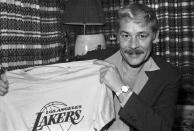FILE - In this June 18, 1981 file photo, Jerry Buss holds a Los Angeles Lakers shirt in Los Angeles. Buss died Monday, Feb. 18, 2013. Buss, the Lakers' playboy owner who shepherded the NBA franchise to 10 championships, has died. He was 80. Bob Steiner, an assistant to Buss, confirmed Monday, Feb. 18, 2013 that Buss had died in Los Angeles. Further details were not available. (AP Photo/File)