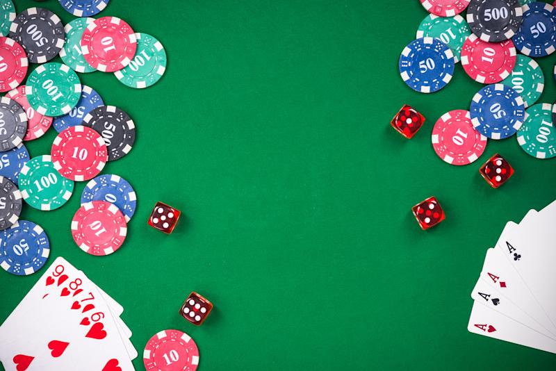 Gaming table with gaming chips, dice, and playing cards.