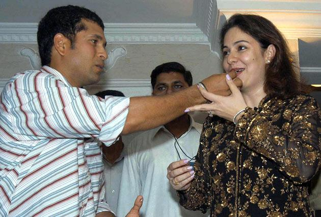 Indian cricketer Sachin Tendulkar (L) gives a piece of cake to his wife Anjali on the eve of his 31st birthday in Bombay, 23 April 2004.  Tendulkar had a get-together with family and friends as he will be attending the wedding reception of his colleague Virender Sehwag who recently got married in Delhi.  AFP PHOTO