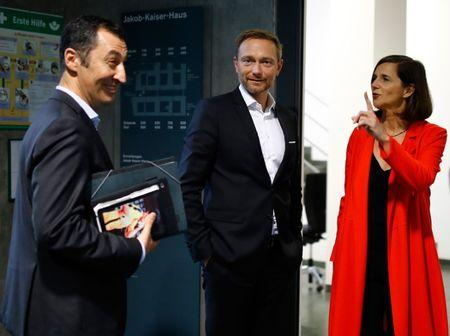 The leaders of Germany's Greens Party, Cem Oezdemir and Katrin Goering-Eckardt chat with Germany's Free Democratic Party (FDP) leader, Christian Lindner, as they arrive at the German Parliamentary Society offices before the start of exploratory talks about forming a new coalition government in Berlin, Germany, October 20, 2017. REUTERS/Axel Schmidt