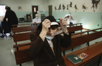 Sister Mary Carol Kardell, of the Felician Sisters of North America, puts on goggles after morning Mass at St. Anne Home in Greensburg, Pa., on Thursday, March 25, 2021. The community has lost 21 nuns to the coronavirus in four convents across the United States, including Sister Mary Evelyn Labik of St. Anne. (AP Photo/Jessie Wardarski)
