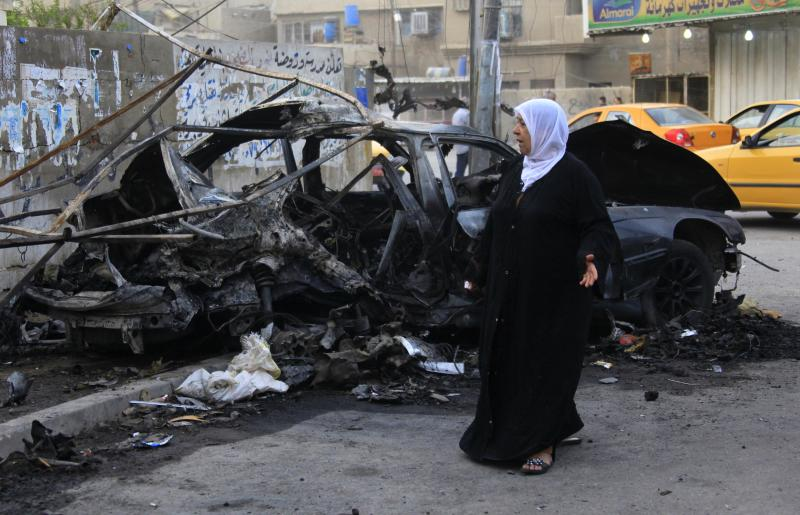 A woman inspects the site of a deadly car bomb attack that killed her sister, in Baghdad, Iraq, Saturday, Oct. 19, 2013. Police officials said the Friday night blast took place in the capital's eastern Mashtal neighborhood. Violence in Iraq has escalated sharply since April, 2013 following a deadly crackdown by security forces on a camp for Sunni protesters in the northern town of Hawija. (AP Photo/Hadi Mizban)
