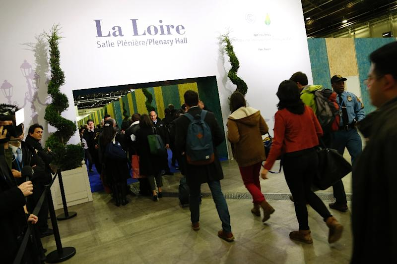 "Attendees enter the plenary hall at the Paris climate summit, aka COP21, in Le Bourget, north of Paris, on November 29, 2015, as French Foreign Minister Laurent Fabius told delegates ""We have to decide how we will be living together on this planet"" (AFP Photo/Thomas Samson)"