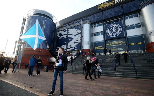 A young Scotland fan waves a Saltire flag before the World Cup Qualifying match at Hampden Park