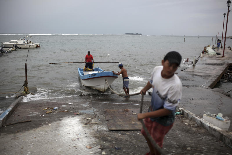 Fishermen drag a boat onto dry land to protect it ahead of the arrival of Tropical Storm Franklin, in the port city of Veracruz, Mexico, Wednesday, Aug. 9, 2017. A strengthening Tropical Storm Franklin took aim at Mexico's central Gulf coast after a relatively mild run across the Yucatan Peninsula, with forecasts saying it would grow into a hurricane before making its second landfall late Wednesday or early Thursday. (AP Photo/Felix Marquez)
