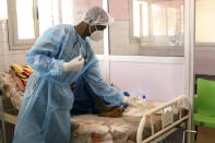 Dr. Dieudonne Wend-Kuni Kientega tends to a COVID-19 patient at Ouagadougou's Bogodogo Medical Teaching Hospital Thursday Feb. 4, 2021. Since November, the conflict-riddled West African nation of Burkina Faso faces a much deadlier second coronavirus wave than the first and health officials worry a lack of knowledge and adherence to coronavirus measures is making it hard to rein in. (AP Photo/Sam Mednick)