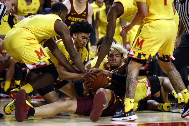 Minnesota forward Jarvis Omersa, bottom, tries to keep possession as he is surrounded by Maryland players in the first half of an NCAA college basketball game, Friday, March 8, 2019, in College Park, Md. (AP Photo/Patrick Semansky)