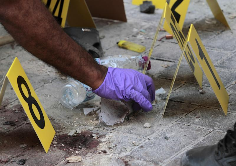 Bahraini policemen collect evidence at the scene of an explosion in Manama, Bahrain, on Monday, Nov. 5, 2012, that killed an Asian man. A series of bomb blasts in Bahrain's capital killed at least two people Monday, authorities said, a sign that some factions within the opposition may be increasingly turning to violence in the nearly 21-month uprising against the Gulf nation's Western-backed rulers. (AP Photo/Hasan Jamali)