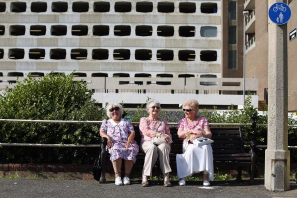 Elderly ladies share a joke as members of the public enjoy the warm weather at the seaside on August 18, 2012 in Worthing, England. Many areas of the UK are experiencing the hottest day of the year so far, with some parts seeing the temperature exceed 32 degrees Celsius. (Photo by Oli Scarff/Getty Images)