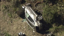 """In this aerial image take from video provided by KABC-TV video, a vehicle rest on its side after a rollover accident involving golfer Tiger Woods along a road in the Rancho Palos Verdes suburb of Los Angeles on Tuesday, Feb. 23, 2021. Woods had to be extricated from the vehicle with the """"jaws of life"""" tools, the Los Angeles County Sheriff's Department said in a statement. Woods was taken to the hospital with unspecified injuries. The vehicle sustained major damage, the sheriff's department said. (KABC-TV via AP)"""