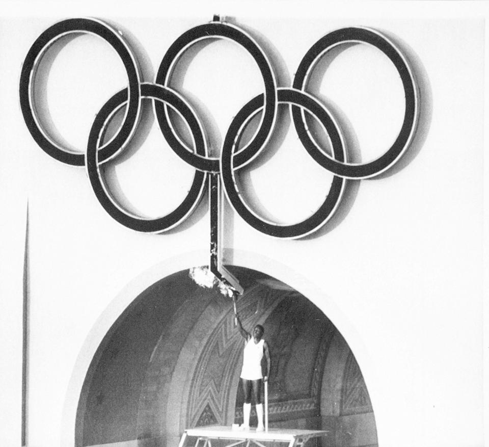 FILE - In this July 28, 1984, file photo, Rafer Johnson, winner of the gold medal for the decathlon in 1960, lights the Olympic torch during opening ceremonies of the Olympic Games in Los Angeles. Rafer Johnson, who won the decathlon at the 1960 Rome Olympics and helped subdue Robert F. Kennedy's assassin in 1968, died Wednesday, Dec. 2, 2020. He was 86. He died at his home in the Sherman Oaks section of Los Angeles, according to family friend Michael Roth. (AP Photo/FIle)