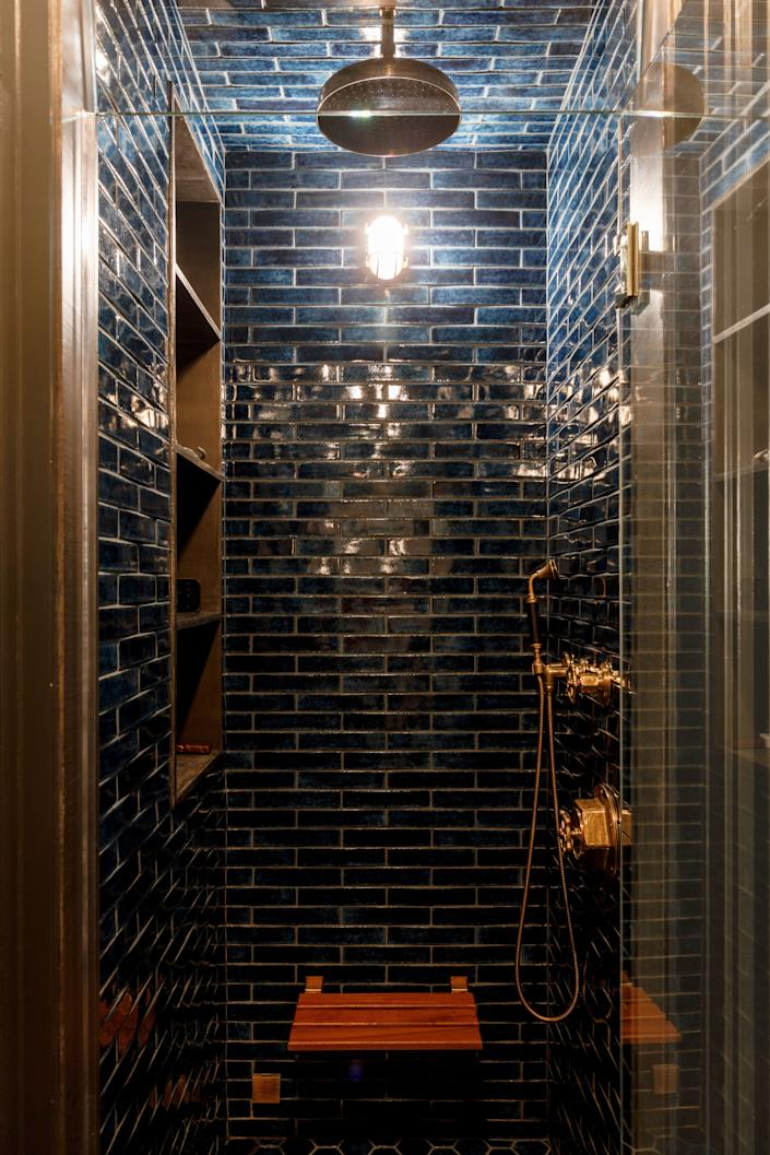 The bathroom, with its rich blue Pecchioli Firenze tiles, is a much moodier space than the rest of the apartment. The shower controls are from Waterworks.