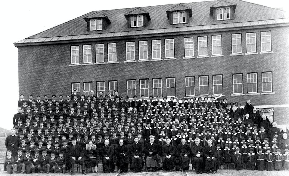 A black and white photo of dozens of Indigenous boys and girls lined up in front of the school while a row of church and school officials sit in the front of the picture.