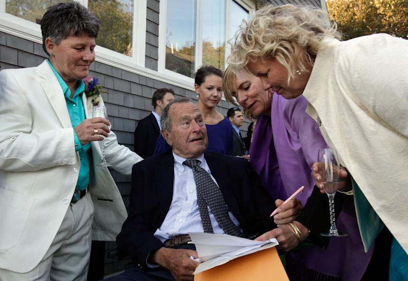 In this Sept. 21, 2013 photo, former President George H.W. Bush, seated center, prepares to sign the marriage license of longtime friends Helen Thorgalsen, right, and Bonnie Clement, left, in Kennebunkport, Maine, as officiant Nancy Sosa, third right, and Helen's daughter Lindsey, rear, look on. Bush was an official witness at the same-sex wedding, his spokesman said Wednesday, Sept. 25, 2013. (AP Photo/Susan Biddle)