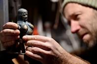 This 15-centimetre tall bronze 'Cicciolina Madonna' is typical of the mini-sculptures he leaves around Budapest for people to discover (AFP Photo/Attila KISBENEDEK)