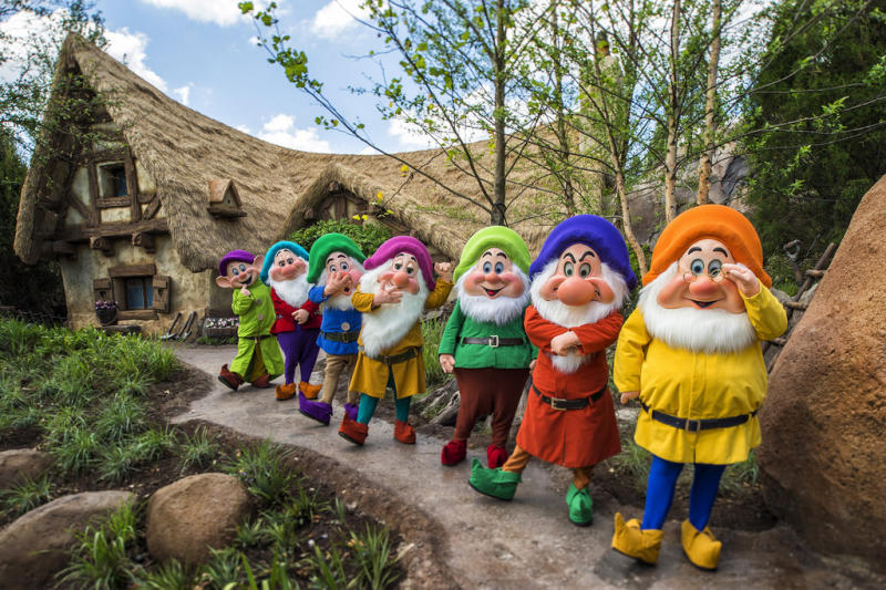 Snow White's seven dwarfs lined up just outside their family coaster attraction.