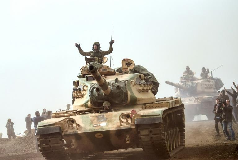 Turkish troops advance near the Syrian border at Hassa, in an offensive aiming to oust a Kurdish militia