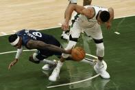 Minnesota Timberwolves' Jarred Vanderbilt and Milwaukee Bucks' Giannis Antetokounmpo go after a loose ball during the first half of an NBA basketball game Tuesday, Feb. 23, 2021, in Milwaukee. (AP Photo/Morry Gash)