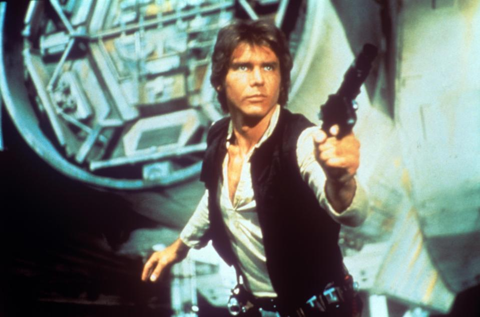 """Harrison Ford in <em>Star Wars</em>. The original 1977 print caption for this photo says, """"In a scene from George Lucas's epic space opera <em>Star Wars</em>, the American actor Harrison Ford as rebel smuggler Han Solo draws a gun against enemies; behind him can be seen a fantastic space shuttle."""" (Photo: Everett Collection/Mondadori Portfolio)"""