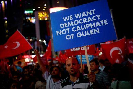 A man holds a banner as he and others have gathered in solidarity night after night since the July 15 coup attempt in central Ankara, Turkey, July 27, 2016. REUTERS/Umit Bektas