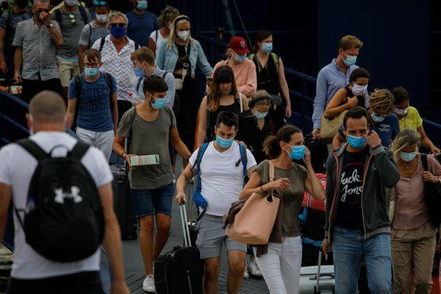 Passengers wearing protective face masks disembark a ferry upon its arrival on the Greek island of Mykonos on October 8, 2020. - The tourism industry in Greece has been hit hard during the Covid-19 pandemic. (Photo by David GANNON / AFP) (Photo by DAVID GANNON/AFP via Getty Images) (Photo: DAVID GANNON via Getty Images)