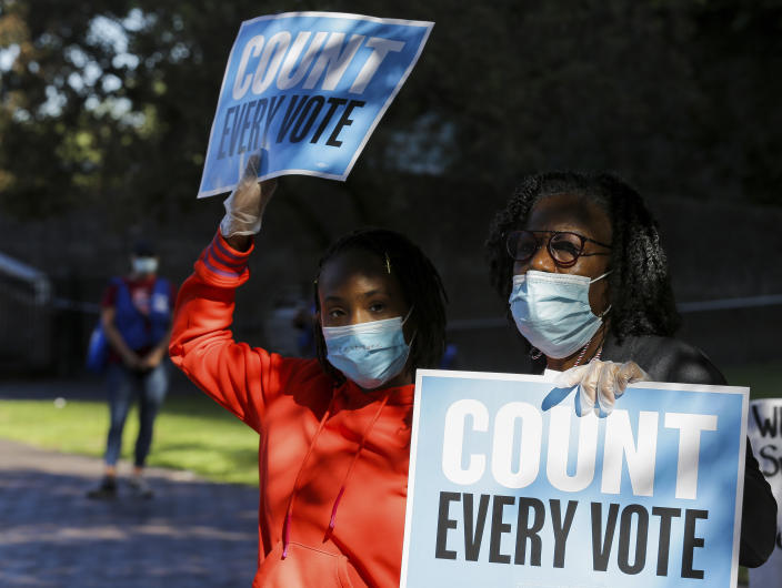 Pearl Wright, right, and her granddaughter Kayin Coward hold up signs alongside fellow demonstrators who gathered outside the Bob Casey Federal Courthouse to voice their support of drive-through voting, which was available as an option to cast ballots for early voters in Harris County, on Monday, Nov. 2, 2020, in Houston, Monday, Nov. 2, 2020.  (Godofredo A. Vásquez/Houston Chronicle via AP)