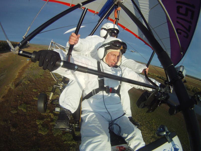 FILE - In this Wednesday Sept. 5, 2012,  file photo Russian President Vladimir Putin, foreground, flies in a motorized hang glider alongside a Siberian white crane, on the Yamal Peninsula, in Russia.  Putin has become alternately notorious and beloved for an array of adventurous stunts, including posing with a tiger cub and riding a horse bare-chested.  (AP Photo/RIA-Novosti, Alexei Druzhinin, Presidential Press Service)