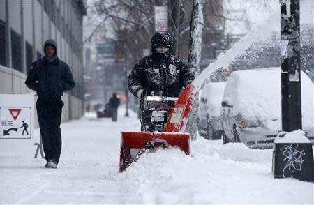 A man clears snow with a snow blower in the South Bronx section of New York City, January 3, 2014. REUTERS/Mike Segar