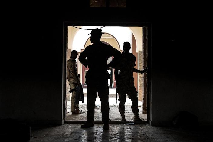 Nigerian troops inspect the former emir's palace in Bama that was used by Boko Haram as their headquarters but was burnt down when they fled, March 25, 2015 (AFP Photo/Nichole Sobecki)