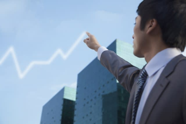 Chinese businessman drawing line graph in sky