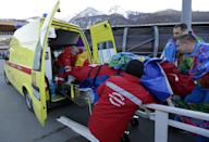 A track worker is loaded into an ambulance after he was injured when a forerunner bobsled hit him just before the start of the men's two-man bobsled training at the 2014 Winter Olympics, Thursday, Feb. 13, 2014, in Krasnaya Polyana, Russia. (AP Photo/Charlie Riedel)
