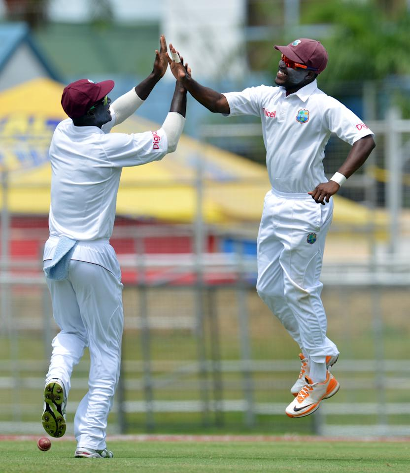 West Indies cricketers Darren Bravo (R) and Darren Sammy celebrate Bravo's catch of Australian batsman David Warner during the fourth day of the second-of-three Test matches between Australia and West Indies April 18, 2012 at Queen's Park Oval in Port of Spain, Trinidad. AFP PHOTO/Stan HONDA (Photo credit should read STAN HONDA/AFP/Getty Images)