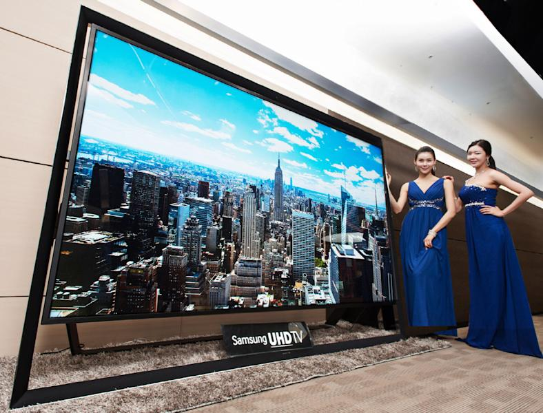 In this undated handout photo released by Samsung Electronics Co. Monday, Dec. 30, 2103, models pose with a Samsung Electronics' 110-inch UHD TV. Samsung on Monday said a 110-inch UHD TV that has four times the resolution of standard high-definition TVs is going on sales for about $150,000 in South Korea. (AP Photo/Samsung Electronics Co.)