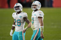 Miami Dolphins quarterback Ryan Fitzpatrick (14) walks off the field with running back Salvon Ahmed (26) during the second half of an NFL football game abasing the Denver Broncos, Sunday, Nov. 22, 2020, in Denver. The Bronco won 20-13. (AP Photo/David Zalubowski)
