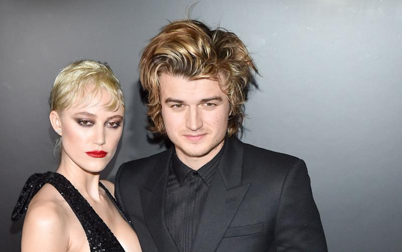 Maika Monroe and Joe Keery attend the Saint Laurent show at Paris Fashion Week. (Photo: Stephane Cardinale - Corbis via Getty Images)