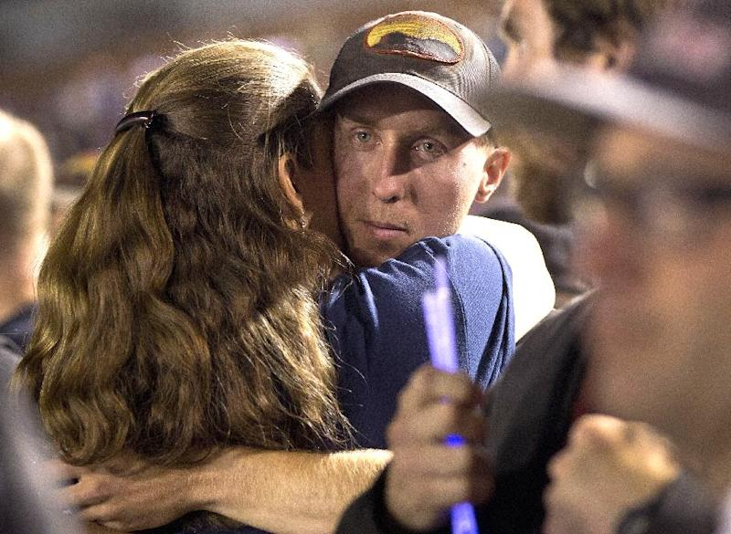 "FILE - In this July 2, 2013 file photo, firefighter Brendan McDonough embraces a mourner near the end of a candlelight vigil in Prescott, Ariz. McDonough, the surviving member of the elite Arizona firefighting crew that was overrun by flames, says he went numb after learning the 19 men he considered his brothers were dead, and he wonders why he alone was spared what he calls a ""horrible, freak accident."" (AP Photo/Julie Jacobson, File)"